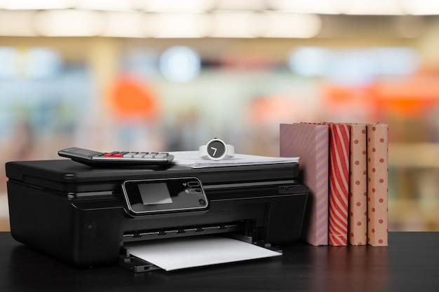 Compacte thuisprinter op bureau met boeken tegen onscherpe achtergrond