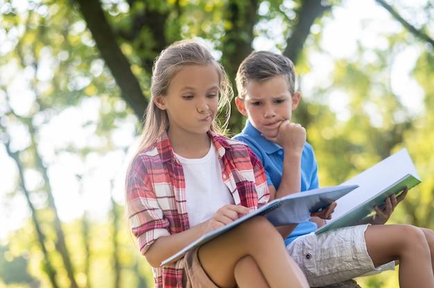 Complex vraagstuk. serieus denkende jongen en meisje van de basisschoolleeftijd met schoolnotitieboekjes die op mooie dag in het park zitten