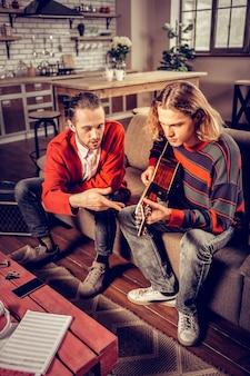 Componeren lied. bovenaanzicht van twee mannen in spijkerbroek die op de bank zitten en een nieuw nummer componeren