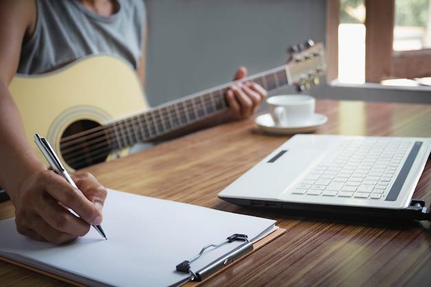 Componist holding potlood en teksten in papier schrijven. muzikant akoestische gitaar spelen.