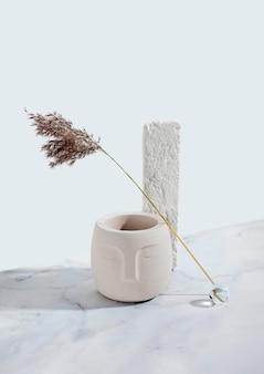 Compositie met betonnen bloempot met boeddha gezicht. buste, standbeeld. pampas gras.