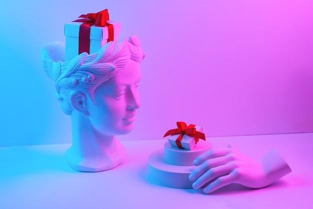 Compositie met buste en hand van gips, doos met rood lint in hoofd en op het podium