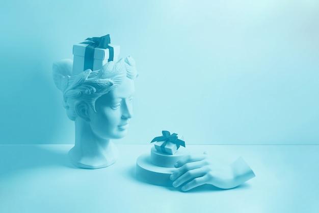 Compositie met buste en hand van gips. een doos met een rood lint in het hoofd en op het podium. cadeau concept.