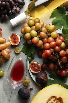 Compositie met druivenmost, wijn, vijgen en meloen op grijs