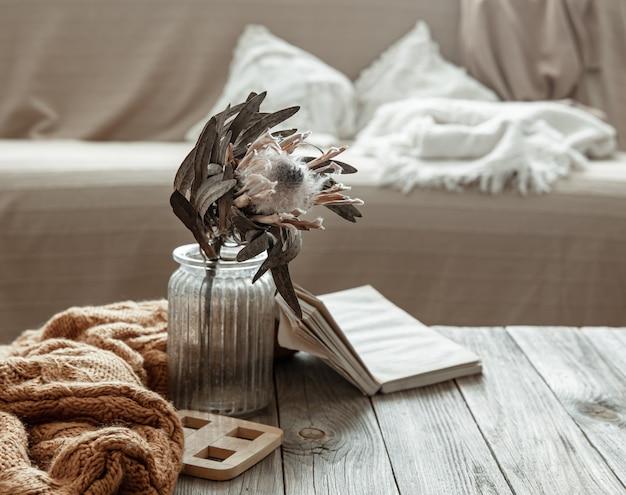 Compositie met een boek, een droge bloem en een gebreid element in het interieur van de kamer
