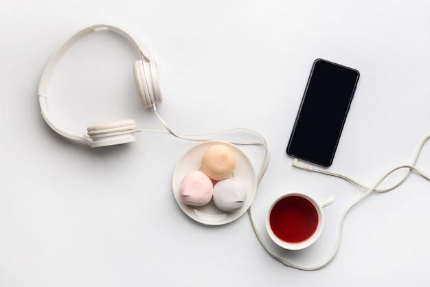 Compositie, met een kopje thee, cake, koptelefoon en een smartphone op een witte muur.