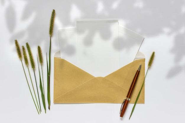 Compositie met gouden envelop witte kaarten pen decoratieve groene planten en schaduw overlay