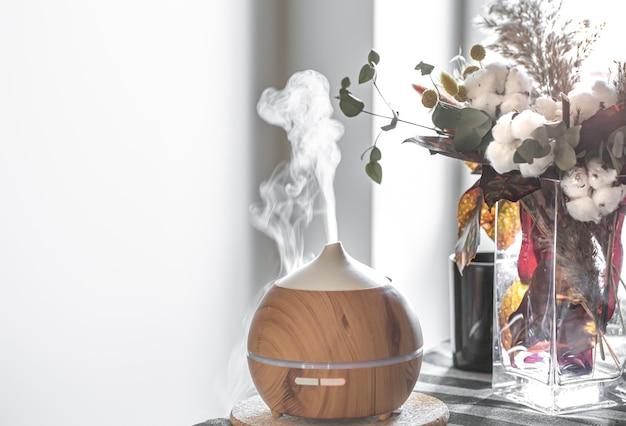 Compositie met luchtbevochtiger en bloemen in een vaas. gezondheidszorg concept.