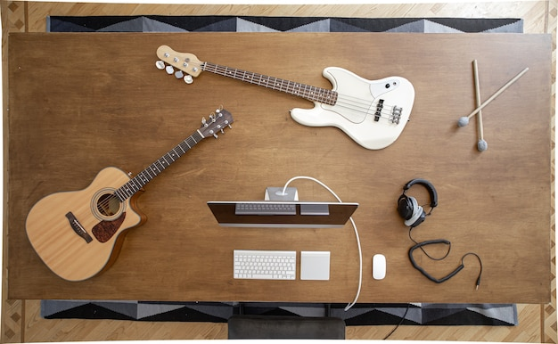 Compositie met muziekinstrumenten op een grote houten tafel in een opnamestudio. werkplek van een muzikant om aan geluid te werken.