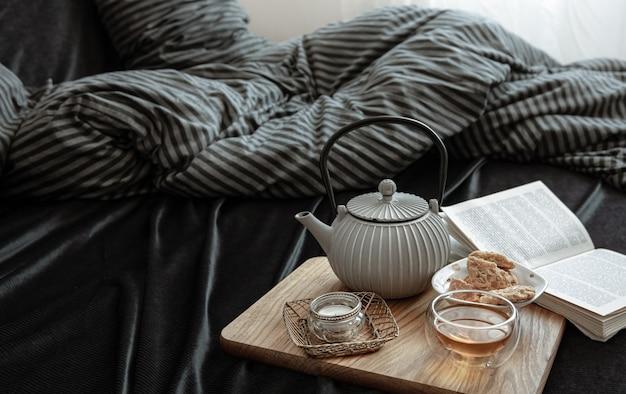 Compositie met thee in een theepot, koekjes, een boek en een kaars in bed