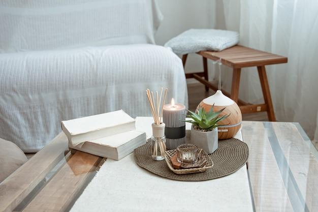 Compositie met wierookstokjes, diffuser, kaarsen en boeken op de tafel in het interieur van de kamer.