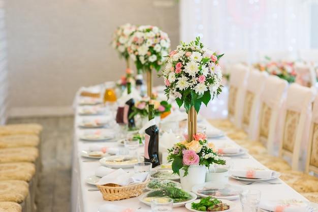 Composities van verse bloemen op de tafel van een feestzaal