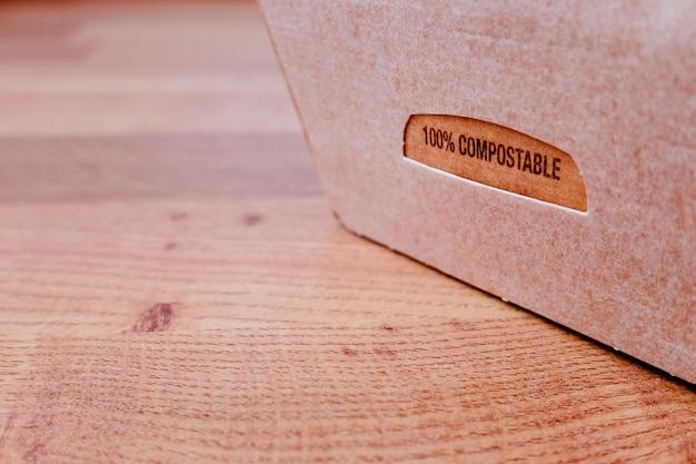 Composteerbare kartonnen doos met voorgekookt voedsel met restanten, klaar om te composteren.