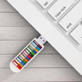 Computer bedrijfsconcept. kleurrijke office-mappen in usb flash drive aangesloten op laptop op een houten tafel. 3d-rendering