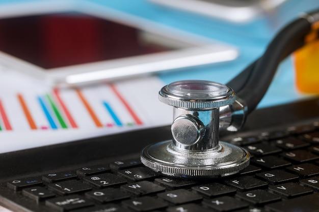 Computer data analyse stethoscoop over een laptop computer toetsenbord gebruikt digitale pro tablet
