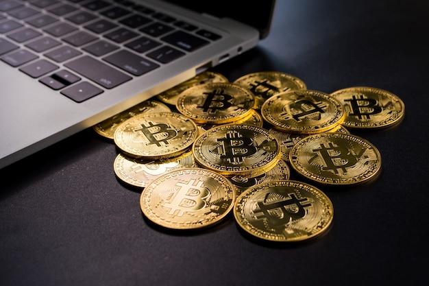 Computer en gouden munten met bitcoin symbool op een zwarte achtergrond.