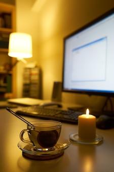 Computer en kopje thee op wit bureau.