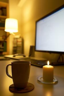 Computer en mok koffie op wit bureau.