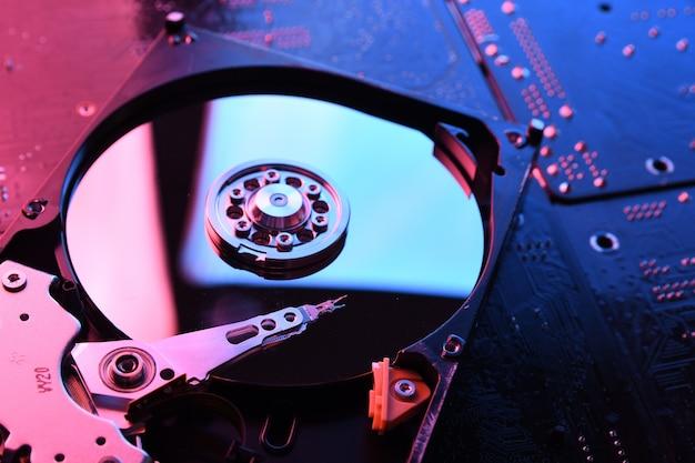 Computer harde schijven hdd, ssd op printplaat, moederbord achtergrond. detailopname. met rood-blauwe verlichting.