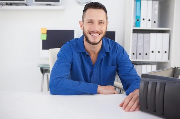 Computer ingenieur zit aan bureau lachend op camera