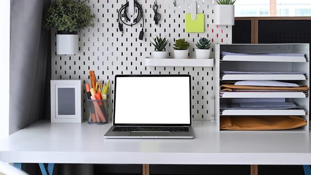 Computer laptop en kantoorbenodigdheden op witte tafel.