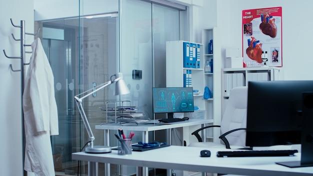 Computer met futuristische mri x ray body scan in moderne lege privékliniek met glazen wanden, hal met lift. behandelingsapparatuur en professionele gereedschappen. spreekkamer, zorgsysteem te