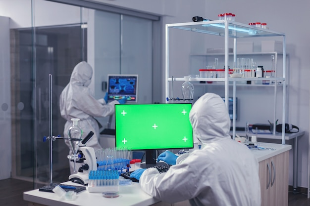 Computer met groen scherm in laboratorium en medisch personeel gekleed in pbm-pak tijdens coroanvirus. team van microbiologen die vaccinonderzoek doen en schrijven op apparaat met chroma key, geïsoleerd, mockup-display.