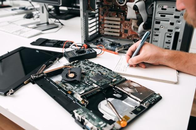 Computer moederbord diagnostiek, close-up. programmeur inspecteert circuit en noteert resultaten op papier. elektronische reparatie, reparatie, renovatie concept