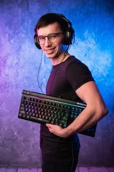Computer nerd met toetsenbord over kleurrijke roze en blauwe neon aangestoken muur