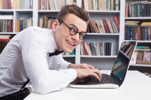 Computer nerd. zijaanzicht van jonge nerd man in overhemd en vlinderdas die iets op de computer typt en met een glimlach naar de camera kijkt