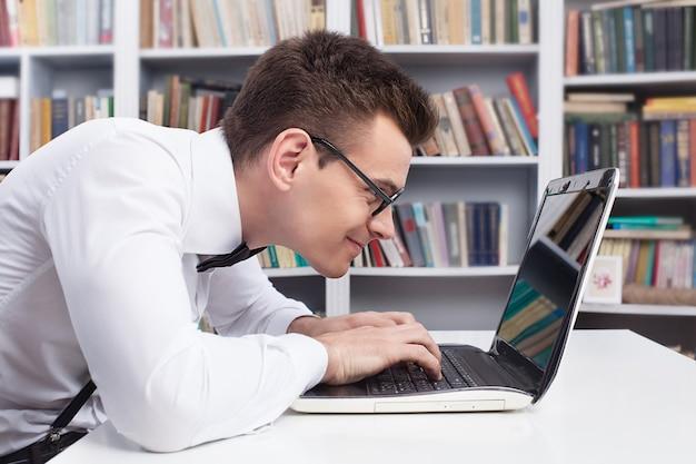 Computer nerd. zijaanzicht van jonge nerd man in overhemd en vlinderdas die iets op de computer typt
