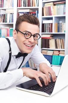 Computer nerd. zijaanzicht van opgewonden jongeman in overhemd en vlinderdas die iets op de computer typt en met een glimlach naar de camera kijkt