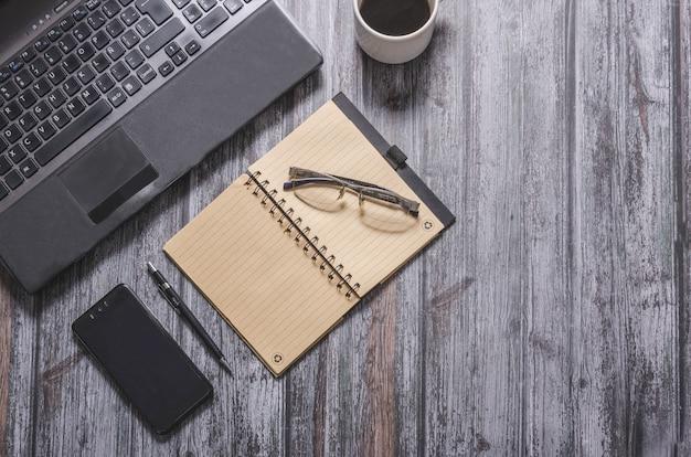 Computer, notebook, telefoon en kantoor op donkere achtergrond
