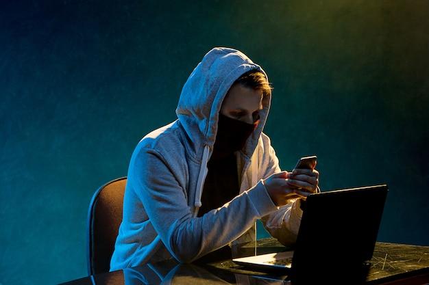 Computerhakker die met een kap informatie stelen met laptop