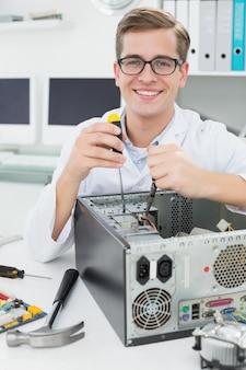 Computeringenieur die aan gebroken apparaat met schroevedraaier werken