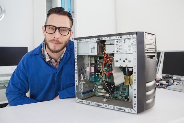 Computeringenieur die bij camera naast open console glimlachen