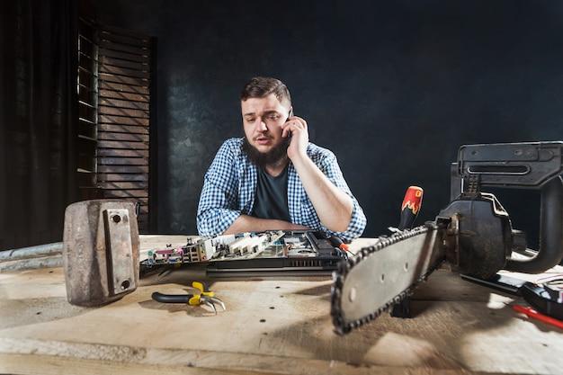 Computeringenieur praat met de klant via de telefoon over probleem met elektronische componenten van laptop. kettingzaag en aambeeld op tafel, technische humor