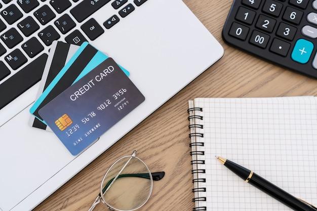 Computerlaptop, creditcards, rekenmachine, notbookpen en glazen op het bureau, rekening en besparingsconcept.