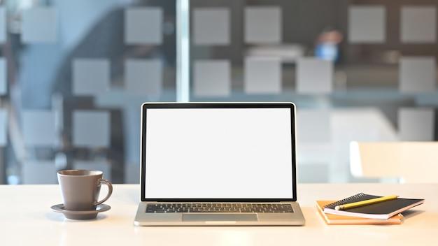 Computerlaptop met het witte lege scherm die op houten lijst met koffiekop en notitieboekje zetten over ordelijke woonkamer.