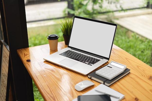 Computerlaptop mock-up afbeelding leeg scherm met rekenmachine op houten tafel in café coworking space