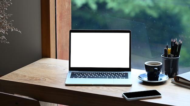 Computerlaptop, slimme telefoonboeken en koffiekopje op houten tafel bij het raam.