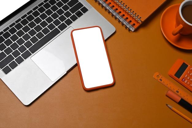 Computerlaptop, smartphone, koffiekopje en notitieboekjes op bruin leer.