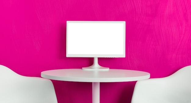 Computermonitor op de witte tafel met twee stoelen op roze paarse muurachtergrond
