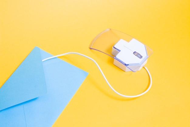 Computermuis en blauwe envelop op een gele achtergrond, kopieer ruimte
