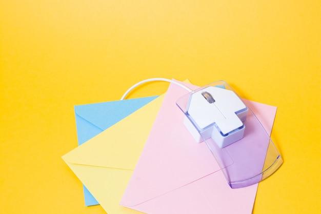 Computermuis en enveloppen op een gele achtergrond, kopieer ruimte