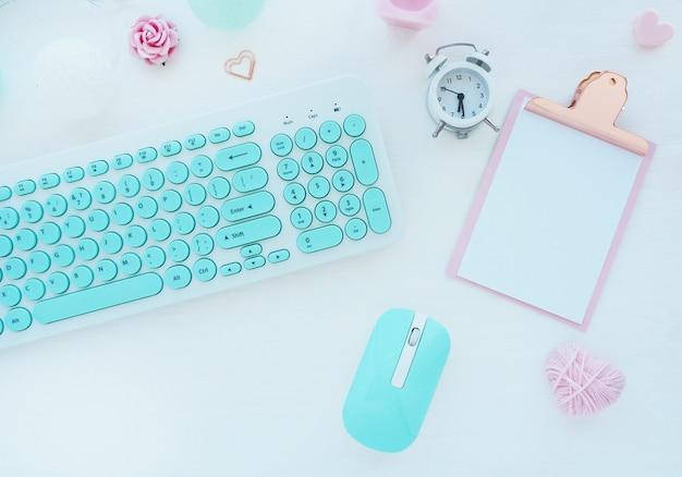 Computermuis en toetsenbord in mint wit, roze klembord, paperclip, kaars, wekker, roze papieren bloem op een witte tafel. plat lag, bovenaanzicht.