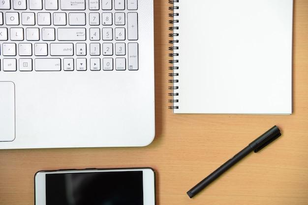 Computernotitieboekje met het bericht van het smartphonelotitieboekje en een pen op werkend bureau in bureau