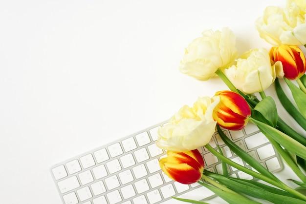 Computertoetsenbord en tulpenboeket. het uitzicht vanaf de top. witruimte voor kopiëren