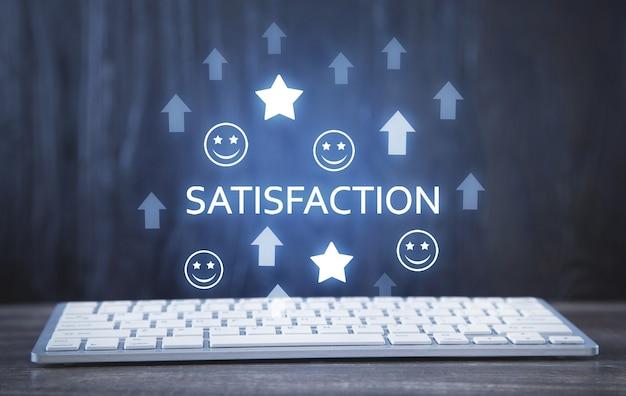Computertoetsenbord op het bureau. groeiende pijlen met een smiley en sterren. tevredenheid. servicebeoordeling