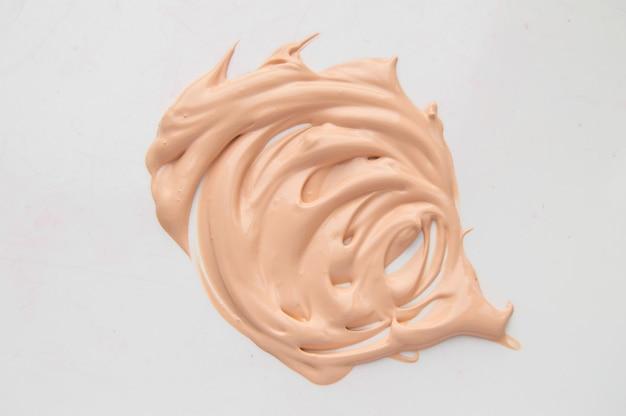 Concealer, lichtbeige make-up, smeer crème basis, foundation op witte achtergrond.